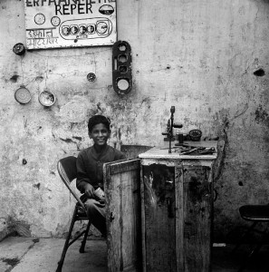 "This boy has his business on a street in New Delhi, India. His service offers the ""reper"" of speedometers. I found the hand drill fastened to the bench amusing. I am quite sure it wasn't there to wind the odometers forward."