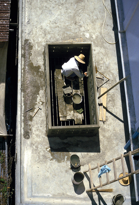 Builder rendering a wall in Bangkok, Thailand.