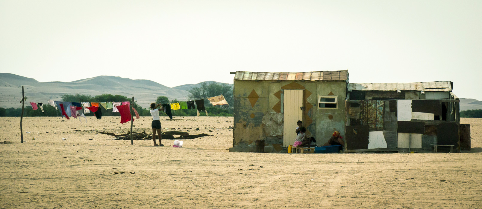 Putting out the washing in the Namib Desert. This is a typical eclectic house, found in the river communities in South-Western Namibia. The people here have ingenious ways of building with whatever materials are available. The ultimate in recycling!