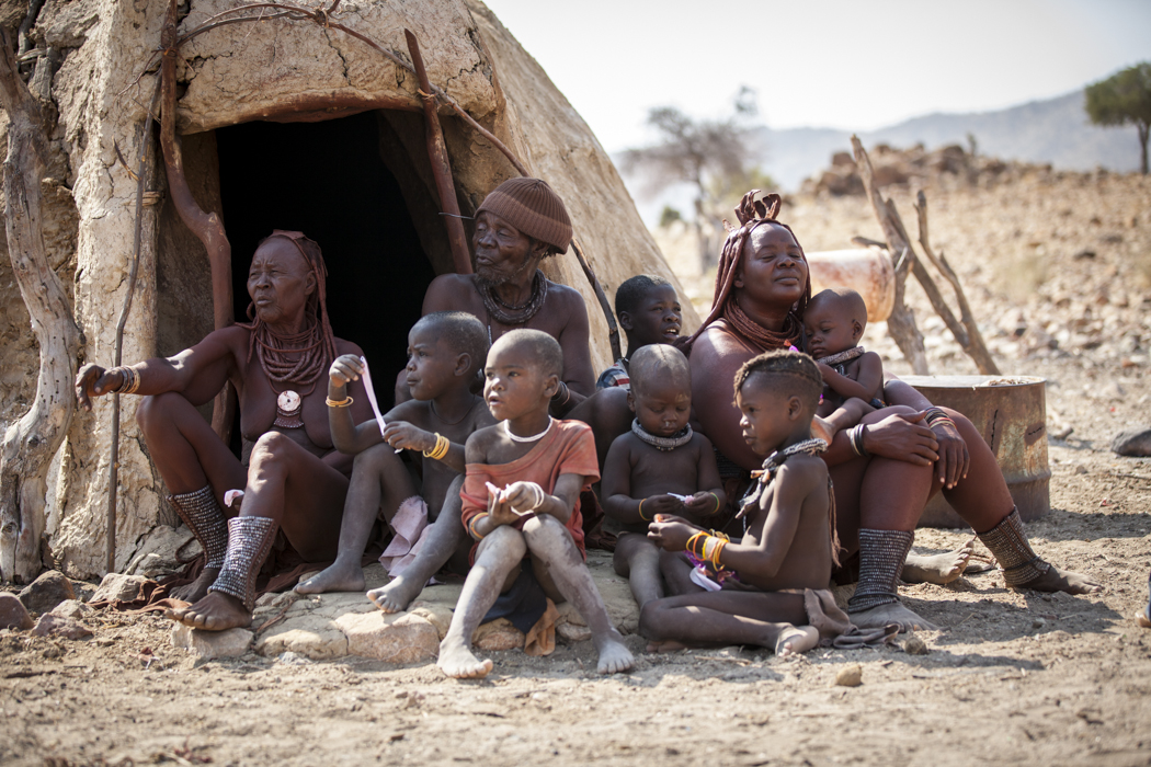 Ovahimba family outside their hut in a village near Opupa Falls. The Ovahimba people are nomadic and villages come and go with their migration.