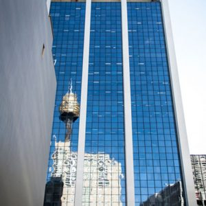 Distorted reflection of Sydney tower in the windows of a Sussex Street building.